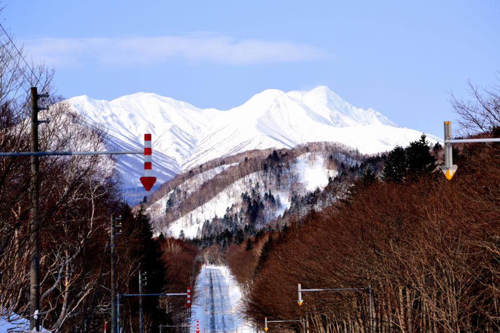 雪に覆われた山々に続く一本道