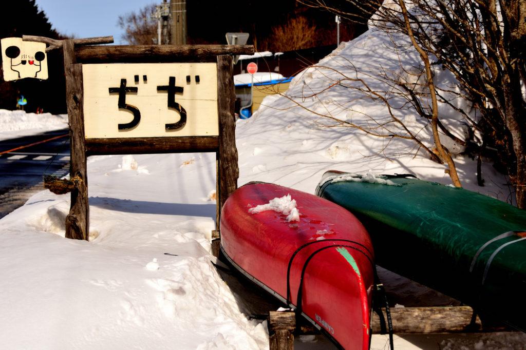 店舗の看板と緑と赤のカヌー