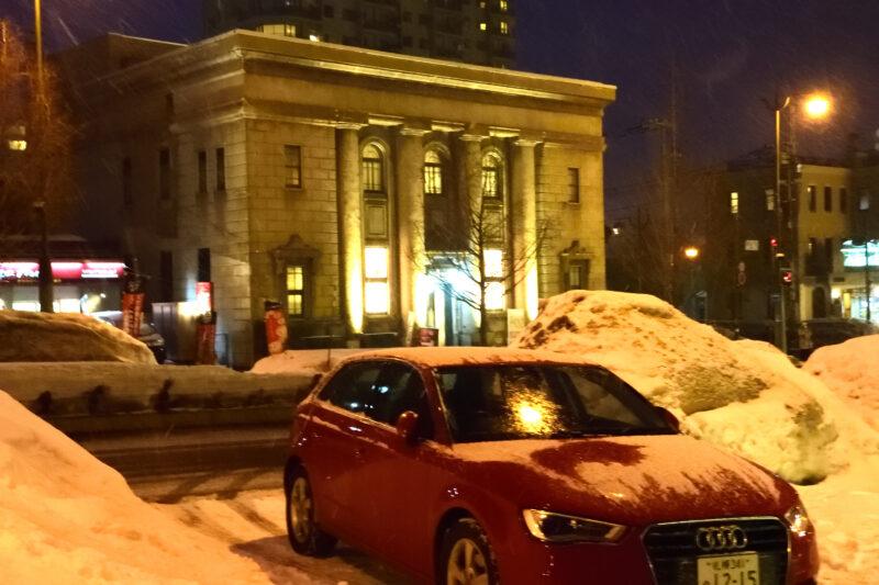 石造りの建物と赤いアウディの車